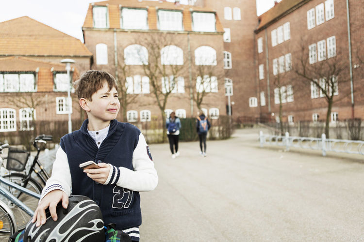Portrait of teenage boy in front of built structure