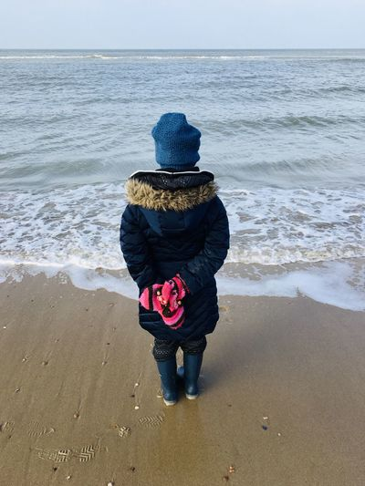 Tourist Destination Sky Sand Water Coast Beach Seascape Tide Woman Girl Sea Beach Water Land Horizon Over Water Real People Horizon Rear View Full Length Hat One Person Leisure Activity Sand Scenics - Nature Beauty In Nature Clothing Sky Casual Clothing Lifestyles Warm Clothing