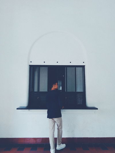 Rear view of young man standing against wall