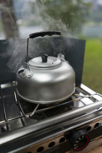 Close-up of tea cup on barbecue grill