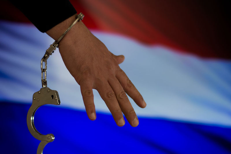 Catch Crime Gun Justice - Concept Leakage Murder Netherlands Blue Body Part Close-up Day Finger Flag Hand Handcuffs  Handgun Human Body Part Human Hand Justice Law Mafia  Men Midsection Prison Thief