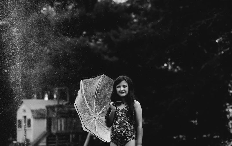 Girl Holding Umbrella While Standing Against Trees