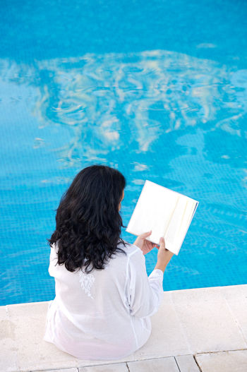 High Angle View Of Woman Reading Book By Swimming Pool