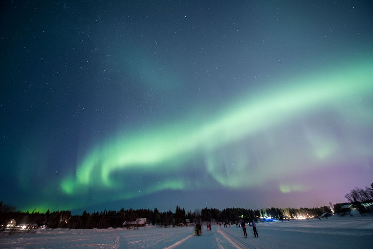 Snow covered field against aurora borealis at night