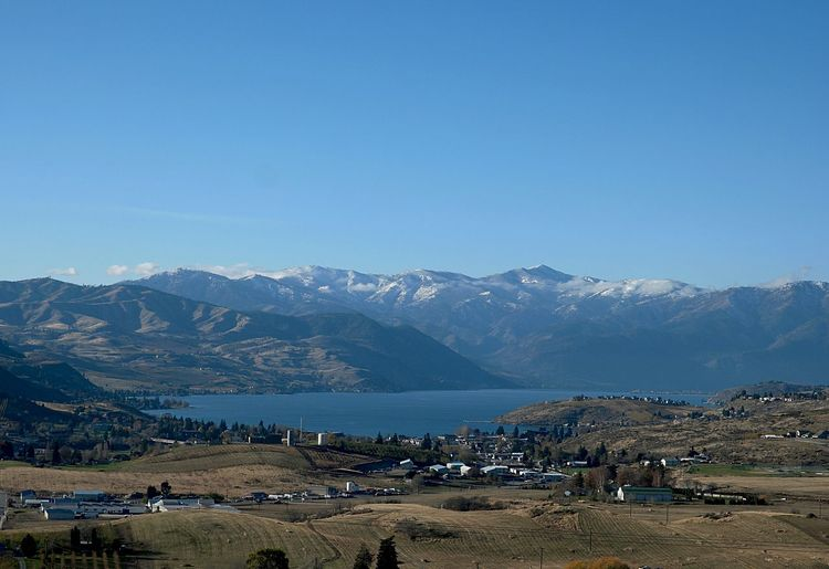 Scenic view of lake chelan and mountains against clear blue sky