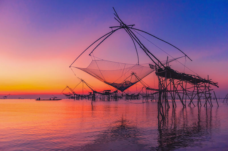 Silhouette fishing net by sea against sky during sunset