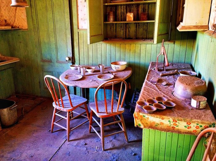 Empty chairs and table in old building