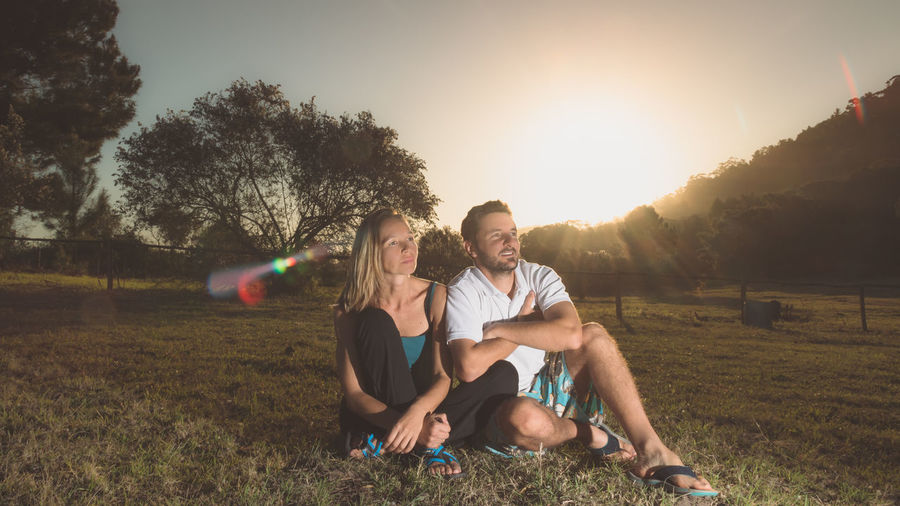 Couple Sitting On Grass In Park At Sunset