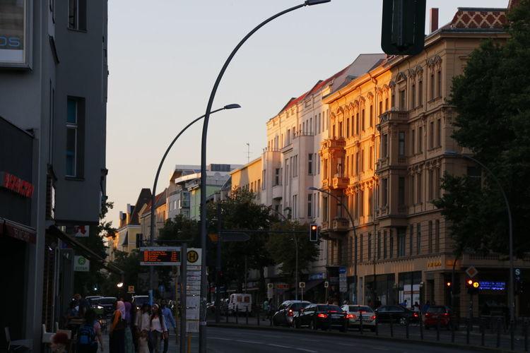 City street and buildings against sky at dusk