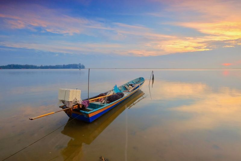 Fishing boats are parked on the beach at sunrise Beauty In Nature Cloud - Sky Lake Mode Of Transportation Moored Nature Nautical Vessel No People Outdoors Reflection Rowboat Scenics - Nature Sinking Sky Sunset Tranquil Scene Tranquility Transportation Water Waterfront