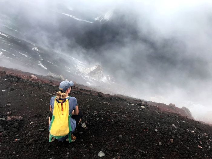 Rear view of mature woman crouching on mountain during foggy weather