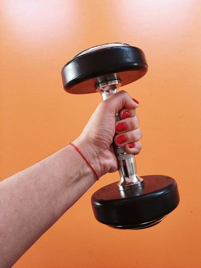 Close-Up Of Woman Holding Dumbbell Against Orange Background