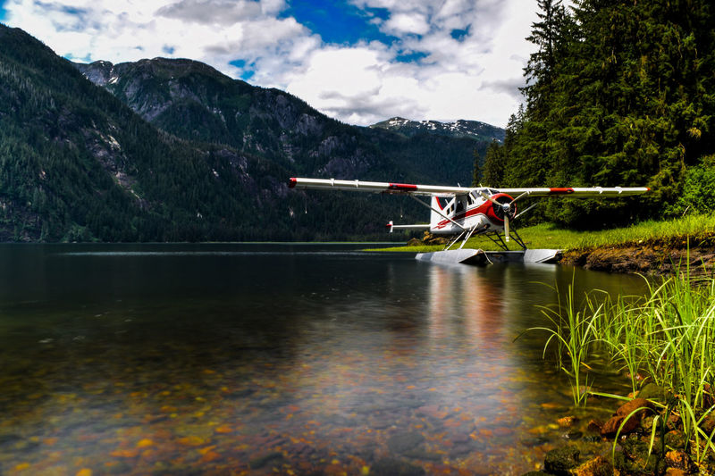 Seaplane on lakeshore against mountains