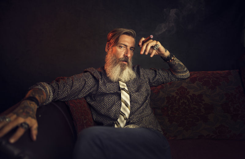 Portrait Of Man Sitting With Cigar Against Black Background