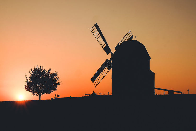 Silhouette traditional windmill against sky during sunset