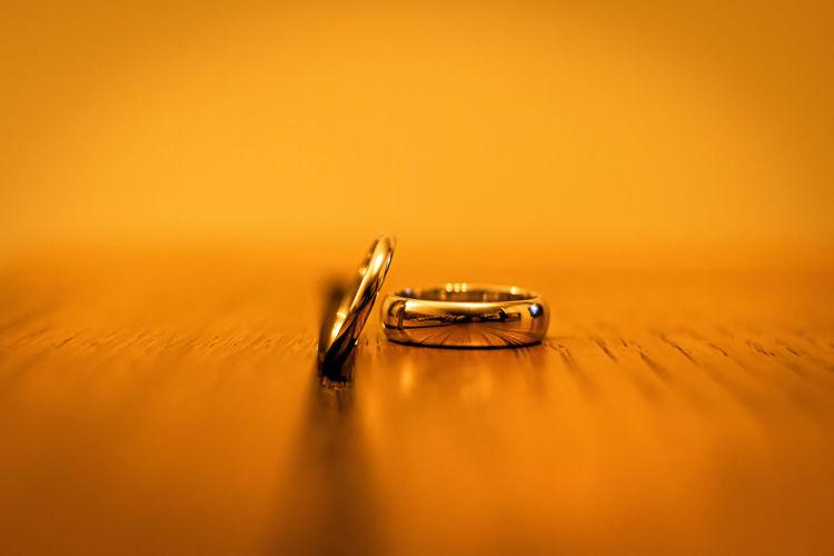 Close-up of wedding rings on orange background