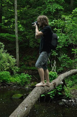 getting the shot Natural Bridge  barefoot Young Man Camera Log Over Water Stream Photographer Working Full Length One Person Nature Water Outdoors Green Son Photographer Young Adult Balancing Green Color EyeEm Nature Lover EyeEmNewHere EyeEm Gallery Eyeem Market EyeEm