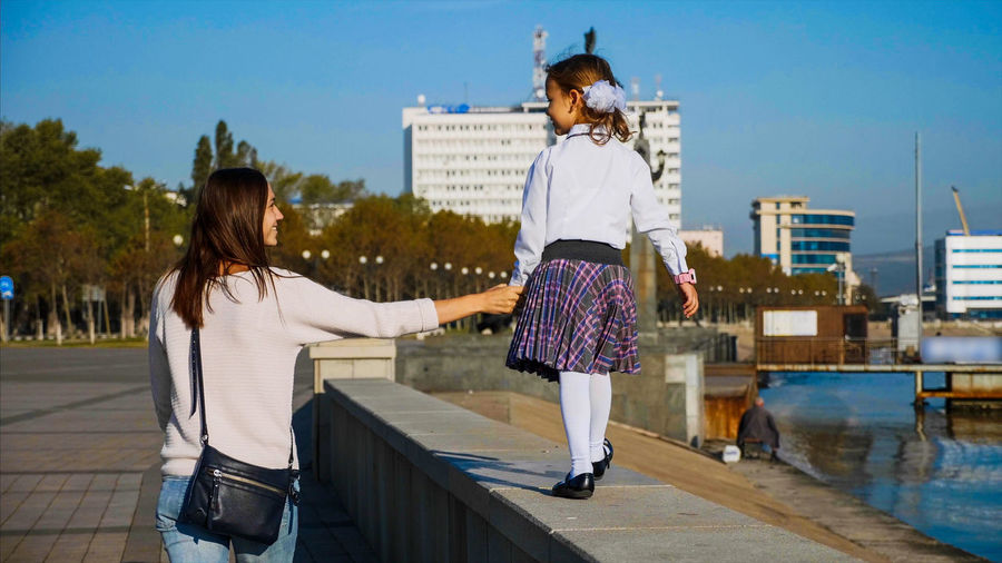 Rear view of mother with daughter walking in city