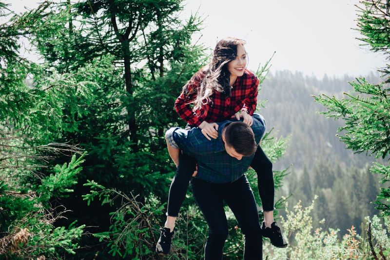 Boyfriend piggybacking smiling girlfriend in forest