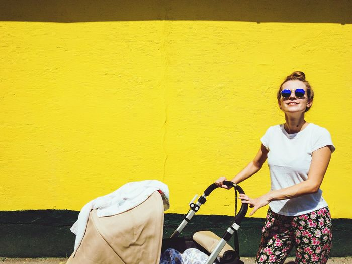 Portrait Of Woman In Sunglasses With Baby Stroller Standing Against Yellow Wall