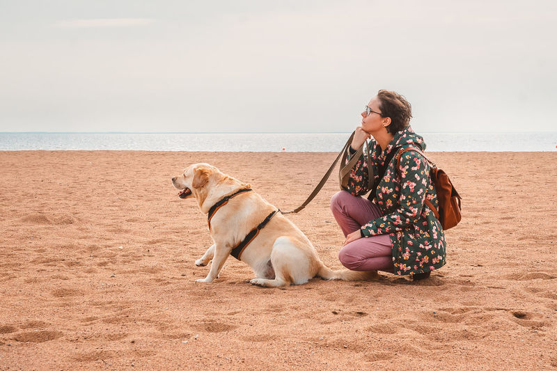 A girl and a labrador retriever sit thoughtfully on a sandy beach in autumn. vacation with a dog