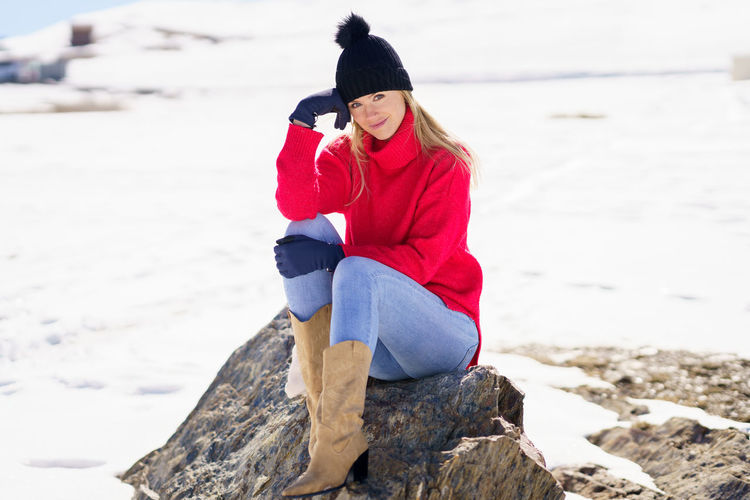 Rear view of woman on rock at beach during winter
