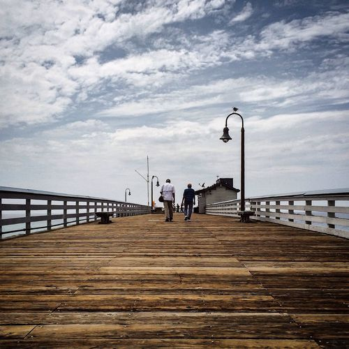 People walking on san clemente pier against cloudy sky