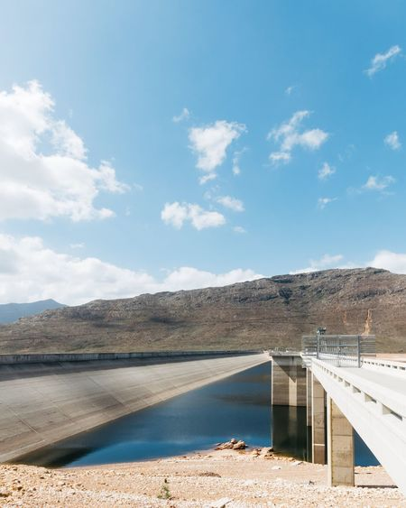 """Cape Town in the Western Cape, South Africa is currently experiencing its worst drought in over a century. This is the Berg River Dam which is just an hour's drive outside of the city centre. It is one of the main sources of water for the 3.78 million residents of Cape Town. The magnitude of the problem becomes clear when one looks at the actual water level compared to the height of the dam wall. We're entering our """"rainy season"""" now. Let's hope things turn around. Africa Nature Drought Dam EyeEm Nature Lover South Africa Cape Town EyeEm Selects EyeEm Gallery EyeEm Best Shots Water Sky Nature Day Cloud - Sky Mountain Beauty In Nature Sunlight Tranquility Scenics - Nature Built Structure Tranquil Scene Land Beach Architecture No People Mountain Range Non-urban Scene Lake Outdoors"""