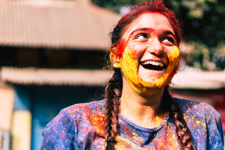 Happy young woman with powder paint on face during holi