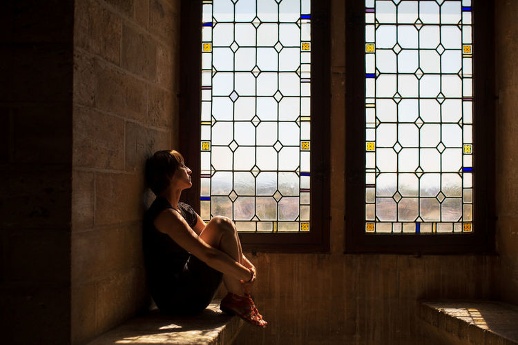 Full Length Of Woman Sitting By Window In Ancient Building