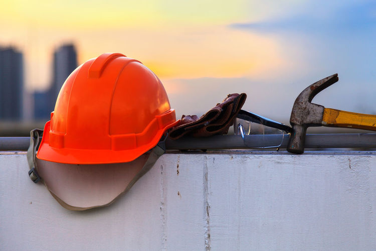 Close-up of red hardhat by hammer and eyeglasses on wall