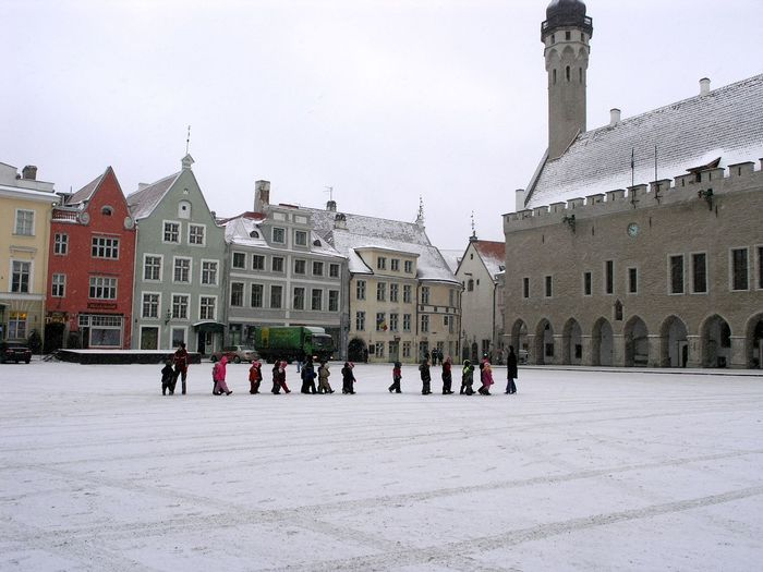 Group of people in town square against buildings in city