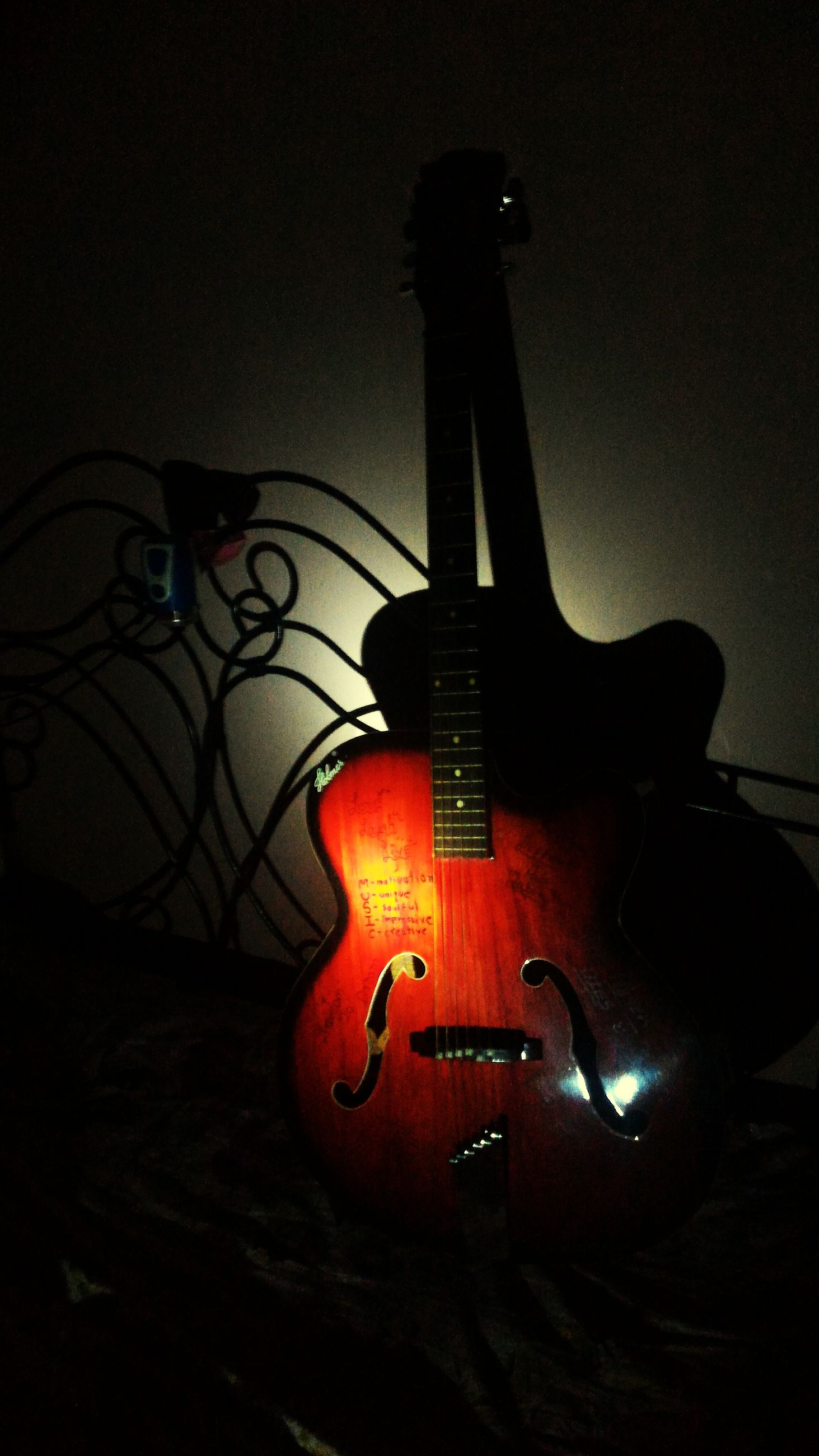 music, musical instrument, illuminated, arts culture and entertainment, low angle view, night, indoors, guitar, lighting equipment, close-up, single object, musical instrument string, electricity, musical equipment, metal, still life, light - natural phenomenon, no people, old-fashioned, technology
