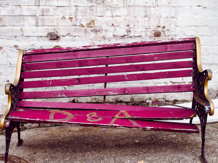 Empty bench against brick wall