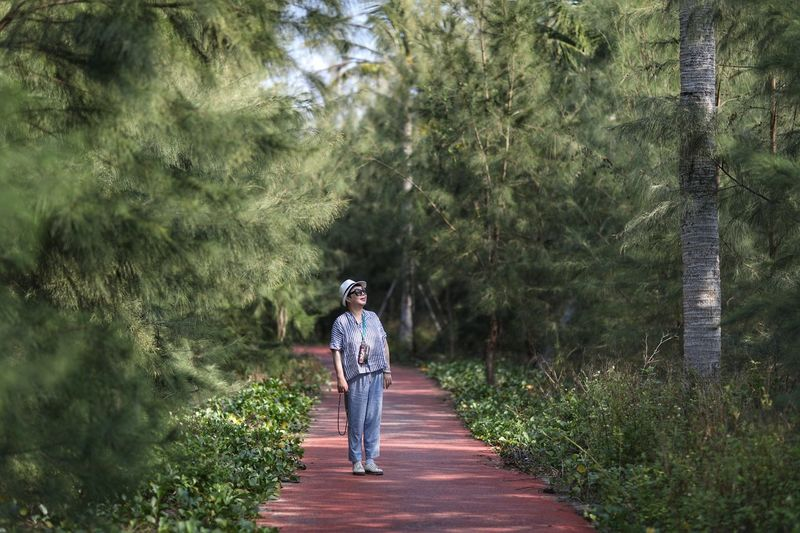 Full length of woman standing on footpath amidst trees in forest
