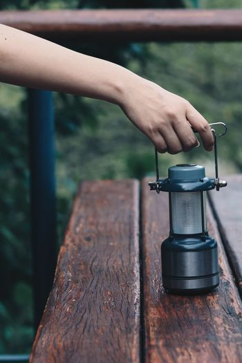 Cropped hand holding lantern on wooden table