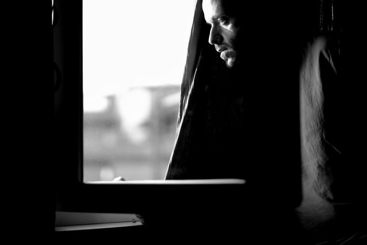 Side view of a man against window