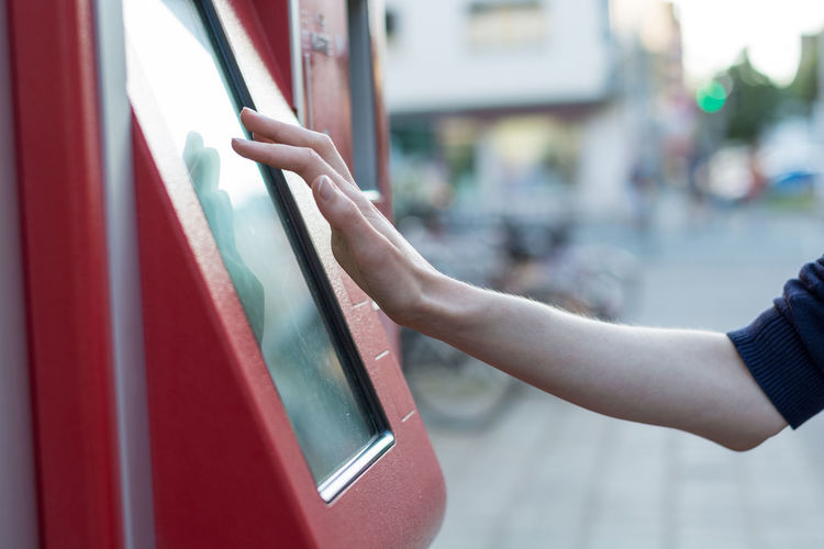 Cropped hand using ticket machine in city