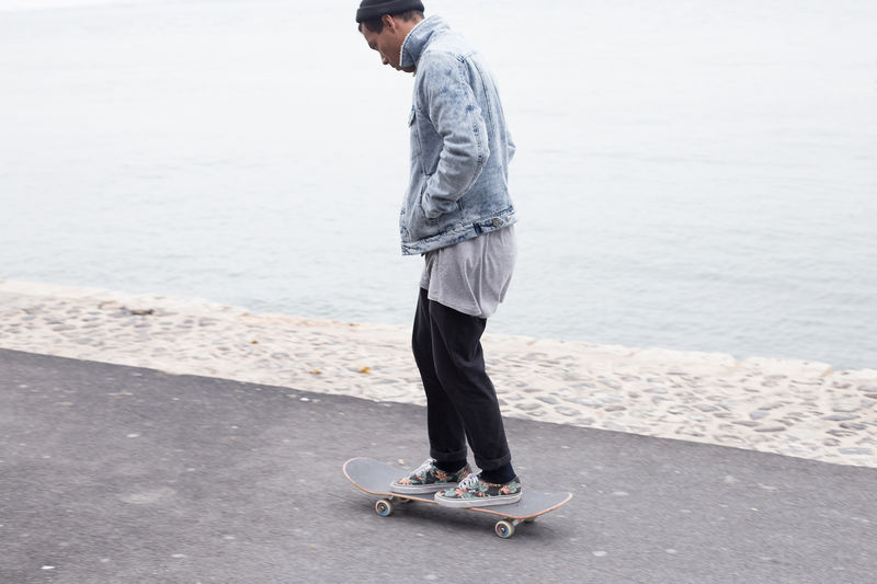 Full Length Of Man Standing On Skateboard