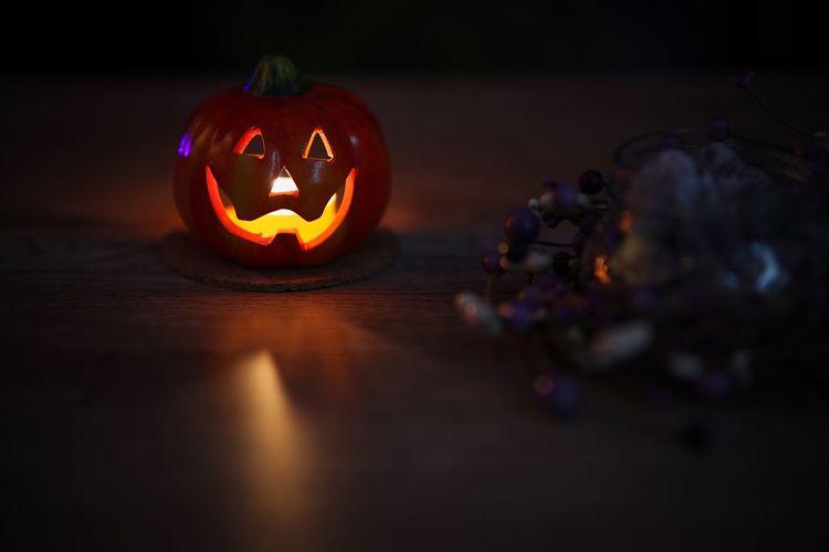 Illuminated pumpkin on table