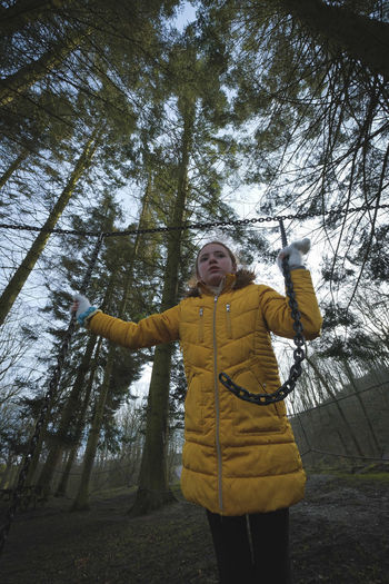 Woman with arms raised in forest