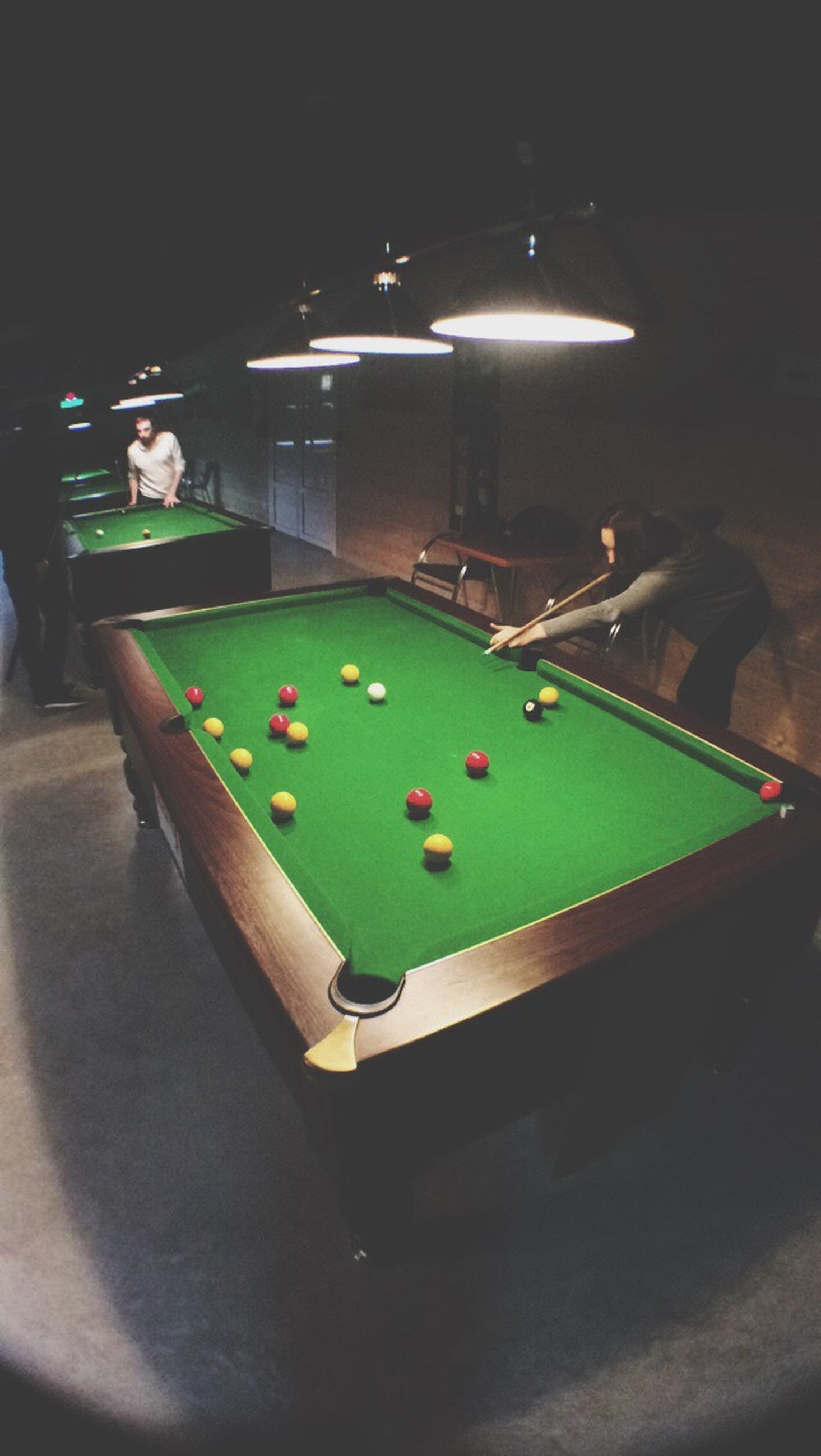 leisure activity, lifestyles, high angle view, green color, indoors, multi colored, men, illuminated, playing, night, sport, fun, sitting, person, blue, arts culture and entertainment, childhood, enjoyment