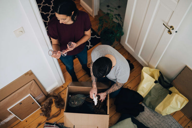 High angle view of couple unpacking box at home