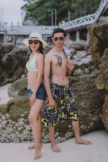 Full length of couple standing at beach
