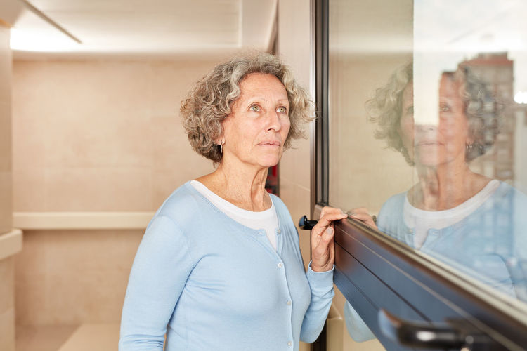 Midsection of woman standing by glass window at home