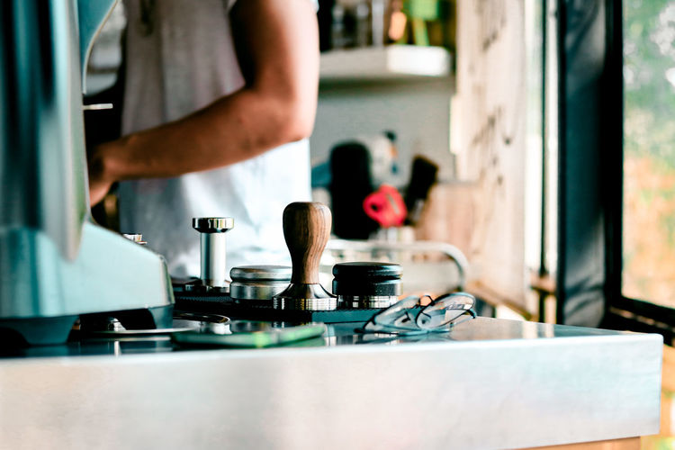 Midsection of man standing in kitchen