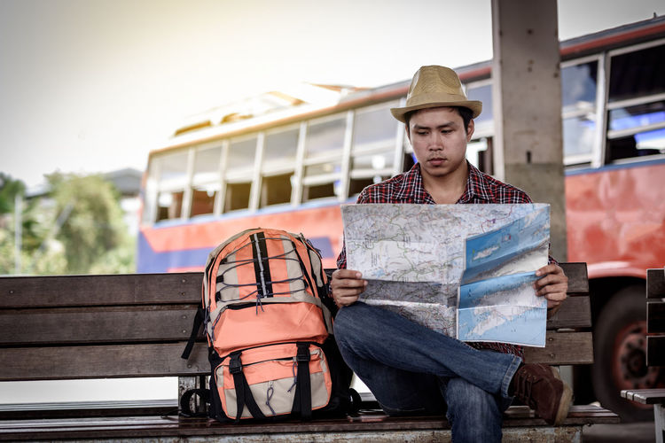 Male tourist holding map while sitting on bench in city