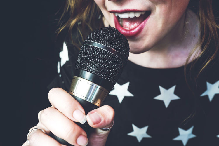 One Person Microphone Input Device Front View Holding Close-up Real People Women Indoors  Music Singing Leisure Activity Lifestyles Smiling Arts Culture And Entertainment Adult Focus On Foreground Happiness Singer  Mouth Open Black Background