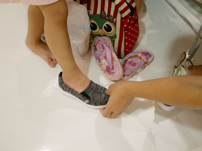 Little baby's foot in a new shoe, trying it on before making a decision whether to buy them Indoors  Lifestyles Hand One Person Women Low Section Child Childhood Girls Holding Females Human Foot Choose Buy Shoes Try On Putting On Wear Shopping Mall Shopping Select