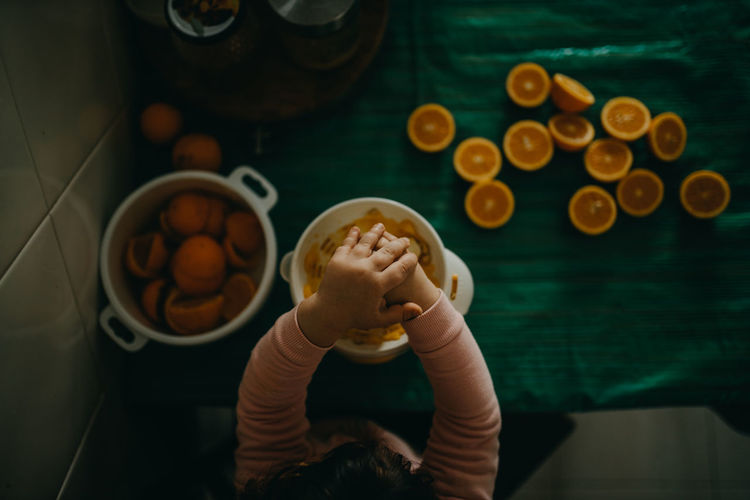 High angle view of hand preparing orange juice on table